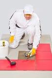 Assoalho adesivo do trowel da telha do trabalhador DIY foto de stock royalty free