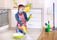 Assoalho da cozinha da limpeza da mulher fotografia de stock royalty free