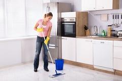 Assoalho da cozinha da limpeza da jovem mulher com espanador fotos de stock