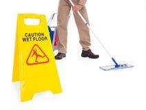 Assoalho da limpeza da vassoura com sinal de aviso Fotos de Stock Royalty Free