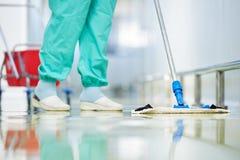 Assoalho da limpeza do trabalhador com espanador Imagens de Stock