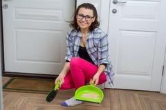 Assoalho da limpeza da mulher com a bandeja da vassoura e da poeira fotos de stock royalty free