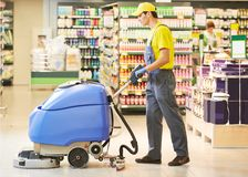 Assoalho da loja da limpeza do trabalhador com máquina Imagens de Stock