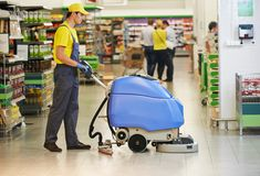 Assoalho da loja da limpeza do trabalhador com máquina Fotos de Stock Royalty Free