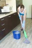 Assoalho de lavagem da moça na cozinha Fotografia de Stock Royalty Free