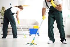 Assoalho de lavagem profissional do grupo de limpeza fotografia de stock