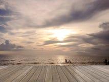 Assoalho de madeira com luz da praia do por do sol, céu bonito, por do sol no mar ilustração royalty free