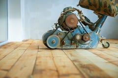 Assoalho de parquet de lustro do trabalhador com máquina de moedura Foto de Stock Royalty Free