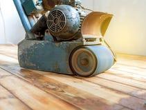 Assoalho de parquet de lustro do trabalhador com máquina de moedura Imagens de Stock