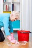 Assoalho idoso da limpeza da mulher fotografia de stock
