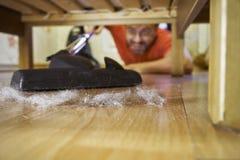 Assoalho limpando do homem de meia idade sob uma cama foto de stock