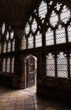Assoalho, paredes, vidro inglês e luz da pedra da catedral vindo através da porta de madeira velha Foto de Stock Royalty Free