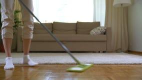 Assoalhos de parquet da limpeza da mulher na sala de visitas Close-up vídeos de arquivo