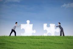 Associé remontant deux morceaux de puzzle Photographie stock