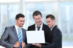 Associés avec un ordinateur portable se tenant dans le lobby du bureau Images stock