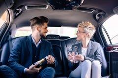 Associés célébrant dans la limousine avec du vin Photos stock