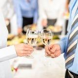 Associés de compagnie en verre de pain grillé d'affaires lors du contact Image stock