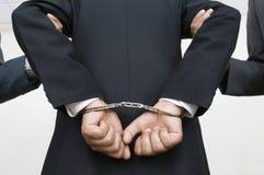 Associés de With Handcuffs While d'homme d'affaires tenant ses bras Images libres de droits