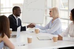 Associés divers se serrant la main lors de la réunion d'affaires, respect concentré photo stock