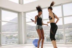 Associés féminins sautant ainsi que la corde à sauter Images libres de droits