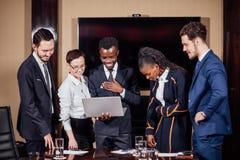 Associés futés à l'aide de l'ordinateur portable lors de la réunion photographie stock libre de droits