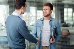Associés gais serrant leur main Photo stock