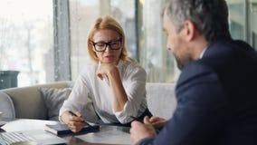 Associés homme gai et femme parlant en café regardant des papiers banque de vidéos