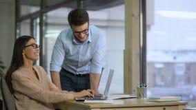 Associés lisant le contrat sur l'ordinateur portable, se réjouissant à l'affaire rentable, démarrage clips vidéos