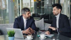 Associés mûrs d'hommes négociant l'affaire parlant utilisant l'ordinateur portable en café banque de vidéos