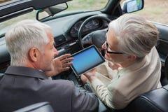 Associés mûrs de sourire travaillant ensemble sur le comprimé dans la voiture chique images libres de droits