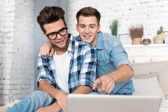 Associés masculins beaux d'orientation non traditionnelle utilisant un ordinateur portable Images libres de droits