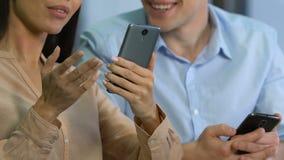 Associés satisfaisants mettant en rouleau l'application mobile, revenu réussi d'affaire clips vidéos