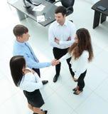 Associés se serrant la main dans le hall de réunion Photographie stock