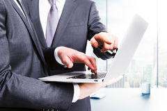 Associés travaillant avec l'ordinateur portable dans le bureau avec la ville vi Photographie stock libre de droits