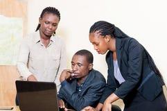 Associés travaillant sur un ordinateur portable dans le bureau Images stock
