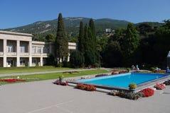 Associação com as camas de água azul e de flor nos lados perto de uma construção bonita na perspectiva das montanhas verdes imagens de stock royalty free