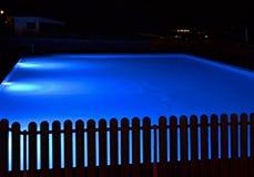 Associação iluminada azul em uma noite com uma cerca preta de madeira no primeiro plano foto de stock