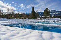 Associações exteriores no tempo de inverno com neve ao redor na área de repouso nevado com o Deckchairs no recurso em Baviera, Al fotografia de stock