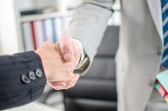 Associados de negócio que agitam as mãos no escritório imagens de stock