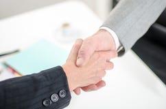 Associados de negócio que agitam as mãos no escritório imagem de stock royalty free