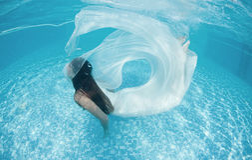 Associação azul do dia ensolarado da nadada subaquática branca bonita do mergulho do vestido da menina da mulher Foto de Stock Royalty Free