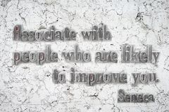 Associate with Seneca. Associate with people who are likely to improve you - ancient Roman philosopher Seneca quote mounted on white marble wall royalty free stock image