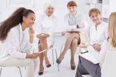 Association of business women. Association of white dressed women sitting together in circle Royalty Free Stock Photography