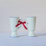 Association et concept de soutien Deux tasses liées à un rouge Images stock