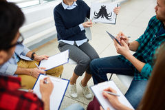 Associations. Female showing Rorschach inkblot to students during explanation Stock Photography