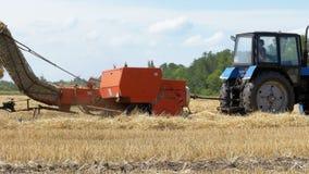 Associazione del raccolto del grano che scarica grano in un rimorchio di trattore durante il raccolto video d archivio