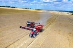 Associazioni e trattori che lavorano al giacimento di grano Fotografia Stock