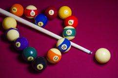 Associe as bolas de bilhar dadas forma em um coração na tabela de feltro do vermelho Imagem de Stock