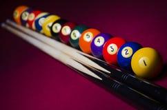 Associe bolas de bilhar em dramático da tabela de feltro do vermelho sombreado Fotografia de Stock Royalty Free