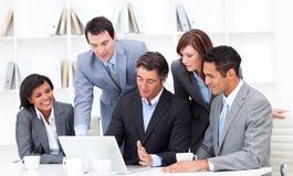 Associés multi-ethniques travaillant à un ordinateur portatif Image libre de droits